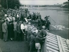 Group of people gathered and looking at working people, who pulling net from the lake. 1957