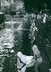 1967  A photo of people bathing and worshiping in the pond.