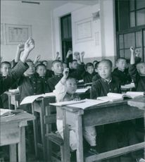 Students in classroom, raising hands and looking towards the teacher.
