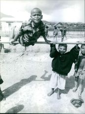 Year ?  A photo of poor children in the village playing and hanging on the pole looking towards the camera.