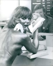A topless woman holding a gold bar during the International Men's and boy's wear exhibition at earis court. 1977