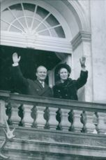 Princess Benedikte of Denmark and Richard, 6th Prince of Sayn-Wittgenstein-Berleburg, waving from a balcony.