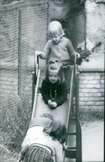 Princess Alexia of Greece and Denmark playing with other children on the slide.