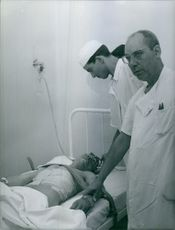 A photo of a doctor and nurses standing and checking up a patient lying on the bed with bandage to  his body.