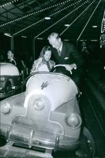 Princess Benedikte of Denmark and Richard, 6th Prince of Sayn-Wittgenstein-Berleburg, ride a bumper car.