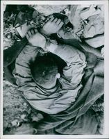 A soldier lying on the ground in Korea.