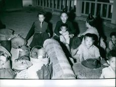 Women sitting outside of their houses with their children and luggage.