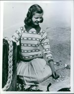 A young girl sitting, looking towards the pebbles and smiling.