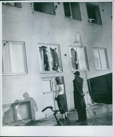 People talking through a broken window of a building after the bombing in Skanstull, Stockholm, during the war, Sweden, 1944.