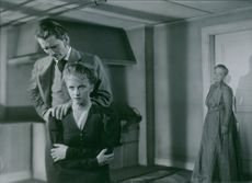 "Vibeke Falk, Lauritz Falk, and Hilda Borgström in a scene from the 1944 Swedish drama film, ""The Clock on Rönneberga""."