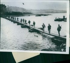 Group of japanese  soldiers passing at the long wood bridge. 1945