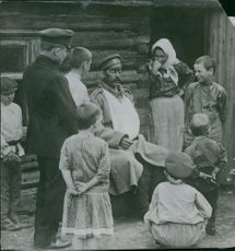 Children and a woman gathered around a man sitting in front of them during the war, 1915.