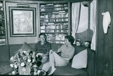 Stavros Niarchos sitting on the couch with Eugenia Livanos.
