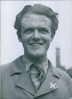 Man celebrating the liberation of Denmark with stickers on his forehead, 1945.