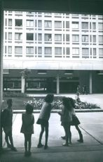 School children standing outside the building talking and laughing.