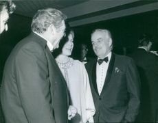 Canadian-American actor Raymond Burr, having a conversation with the couple, Rainier III and Grace Kelly.