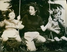 Vintage photo of a mother and her children riding on swing. Photo taken in March 1962.