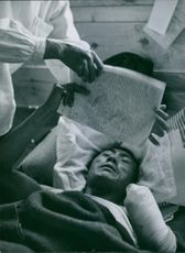 A wounded soldier lying on bed while reading a newspaper during Tyskland war, 1950.