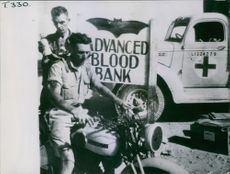 A medical orderly putting a bottle of blood in the rucksack of an eighth Army Dispatch rider from the front line casualty clearing station.  - 1942