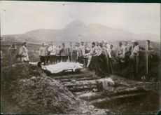Christians doing spiritual activity, gathered around the dead body.