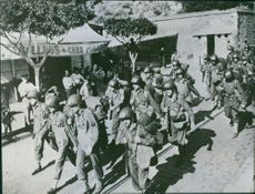 1946 United States soldiers march through a section of Oran, French Algeria, that resembles a street in Southern France.