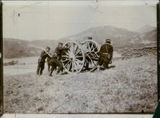 Japanese soldiers pushing cannon to get up a hill during the Russo-Japanese War, 1904.