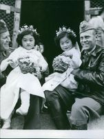 Swedish Captain Sven Dorring and colleague, holding carrying Korean children.