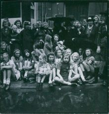 Children siting down together with other people in Freden. 1945.