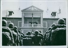 Italian soldiers standing and saluting to their tricolor flag on the royal palace in Cetinje.1941.