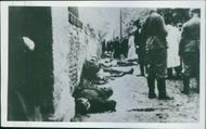 Soldiers standing, while wounded man lying down beside the wall.