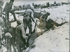 U.S. Military soldiers with guns searching a Japanese Shelter on Tarawa. 1943