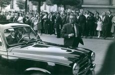 Crowd gathered on the side of the street looking at the man, 1964.