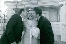1968 - A woman smiling and holding a bouquet of flowers, while being kissed by two men.