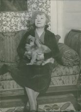 Anna Branting holding a puppy while sitting, 1933.