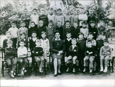 Group of children siting together with their teacher.