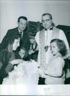 Priest with Foglia twins and family at baptism of younger sibling.
