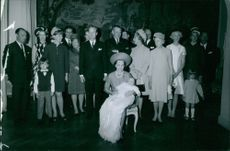 Princess Benedikte sitting on chair, holding her new born baby in her arms, other relatives standing behind smiling.