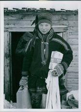 A Sami boy receiving aid from Sweden, oats and beans during the Forced evacuation and burning of Finnmark and North Troms 1944.