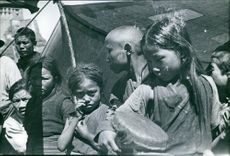 Children gathered in street and looking towards the camera.
