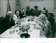 1961  A photo of Marie Besnard with people enjoying meal on the table.