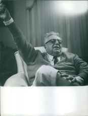 Aga Khan III relaxing in a sofa and hold up one of his hand