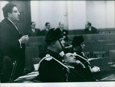 Pierre Jaccoud sitting with guards beside him while his lawyer speaking during the proceedings in court for Jaccoud case. Photo taken on February 1, 1960.