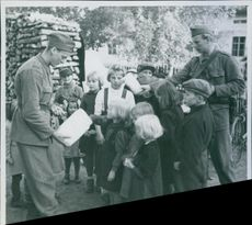 Swedish soldiers cheer up evacuees children with candies.