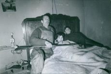 Man siting on the bed with children, holding gun.