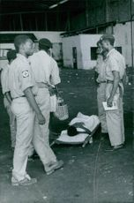 """Medical people helping a young boy lying on a stretcher in Congo.  """"Congo""""  1967"""