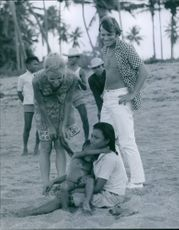 A tourist couple talking with two local children at a beach.