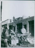 War Damages in Poland Soldiers standing on the roof and loading the scrub on the carrier.
