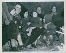 A family group of young Italian children with their mother and father and grandmother smile happily despite the discomforts of the box car in the refugee train which is transporting them back to the hometown in the south.