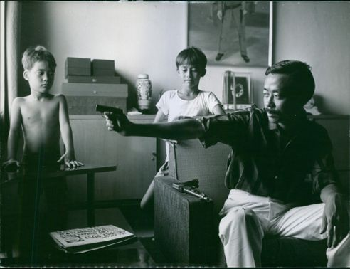 Nguyễn Cao Kỳ pointing a gun at the window, his children looks on. 1965.