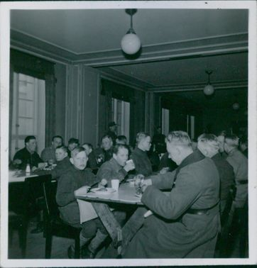 Finnish soldiers and male children eating food in the dining hall. 1940